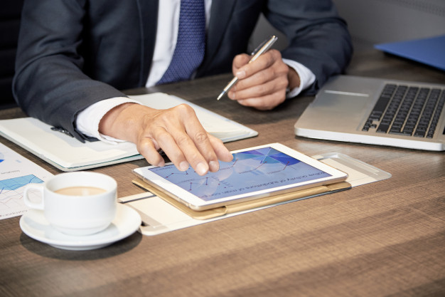 crop-businessman-using-tablet-table_1098-20059
